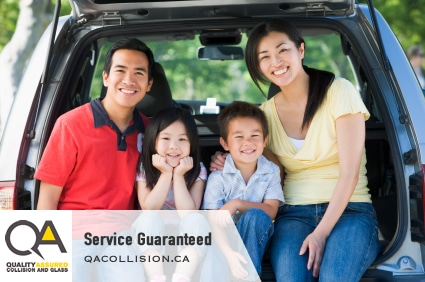 Service Guaranteed - Young Asian family sitting in the open hatch of an SUV
