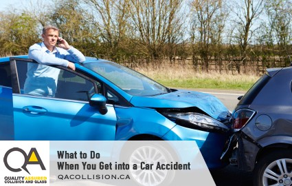 What to Do When You Get into a Car Accident - Man on his cell phone standing by the open door of a blue car that rear ended another vehicle