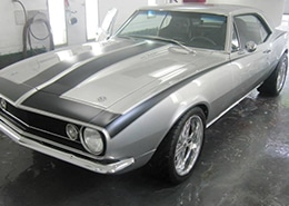 Muscle car in paint booth showing finished custom paint job