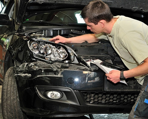 Auto body repairman assessing damage to the front end of a car