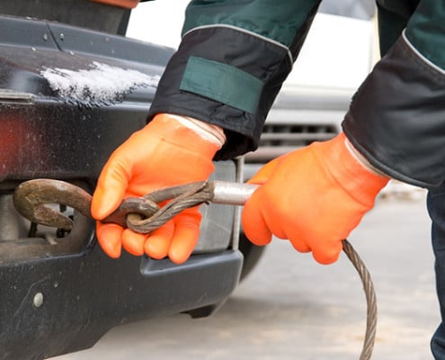 Gloved hands hooking a tow rope to a vehicle