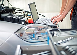 Person with laptop computer running Mechanical diagnostics at the open hood of a car