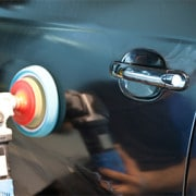 Auto detail person buffing up the paint on the driver side door of a car