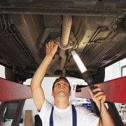 Man performing a Vehicle Inspection beneath a car which is on a car lift