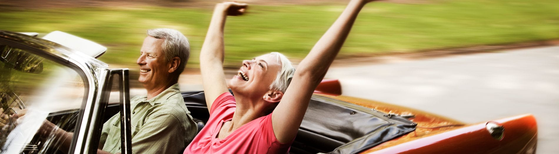 Laughing elderly couple in a red convertible - woman with her hands in the air