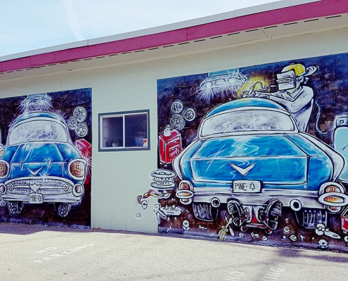 Mural of cars being repaired on the wall of Pinetree Auto Body in Powell River BC