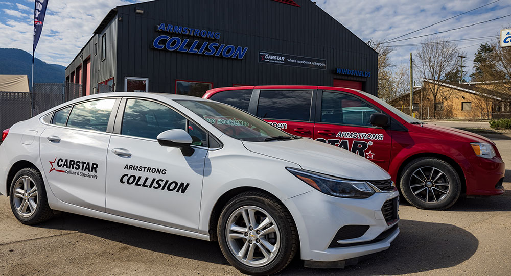 Photo of 2 courtesy cars in front of Armstrong Collision in Armstrong BC